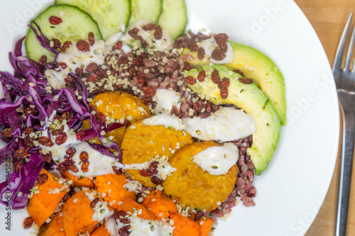 Aluminium Boeddha Vegan buddha bowl with Tempeh, Pumpkin, Red Cabbage, Cucumbers, Avocado and Hempseeds presented on a white plate
