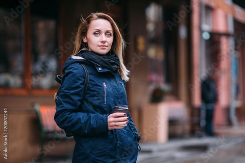 Foto Murales Beautiful happy young woman with a cup of coffee in a winter coat with a knitted fashionable stylish scarf walking in the city