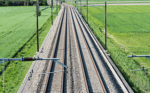 Plexiglas Spoorlijn several railroad tracks leading to the horizon in midst of green fields
