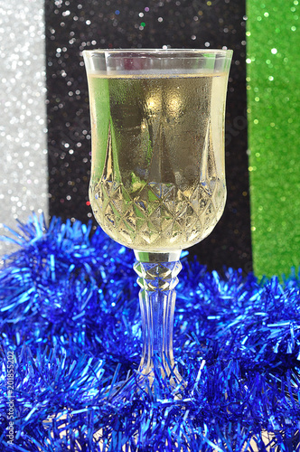 A glass of champagne against a colorful background and blue tinsel