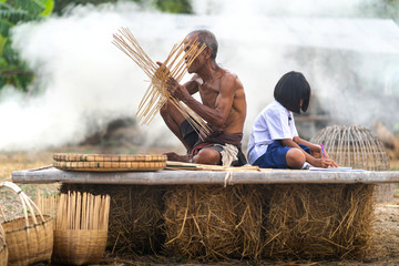 Elderly man and bamboo craft with student girl, lifestyle of the locals
