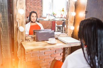 Female client sitting on a chair near the mirror n beauty salon.