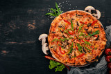 Pizza with chicken and mushrooms. Top view. On a wooden background. Copy space.