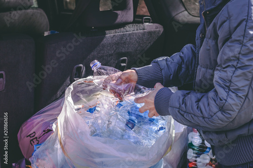 Woman preparing for recycling plastic bottles in the trunk of the car.