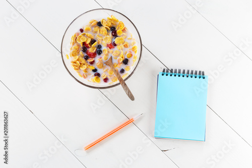 Foto Murales Healthy breakfast from musly and berries in a glass bowl. On a white wooden table, mock up notebook and the pen lies. Top view