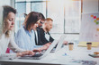 Teamwork process concept.Young coworkers work with new startup project at sunny office.Horizontal, blurred background.