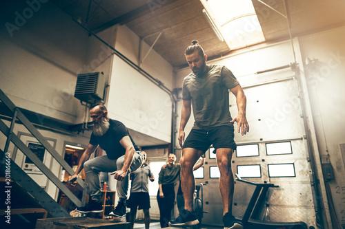 Dwa dopasowywający mężczyzna robi pudełku skaczą wpólnie przy gym