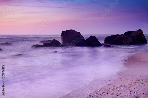Plexiglas Purper Summer seasonal natural vacation background. Romantic morning at sea. Big boulders sticking out from smooth wavy sea. Pink horizon with first hot sun rays. Long exposure.