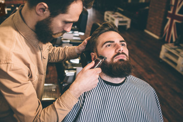 Nice and good hairstylist is cutting some of the customer's beard with an electrical razer. He is doing that very accurate.