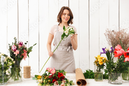 Wall mural Pretty smiling florist woman with different flowers