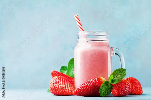 Różowy truskawkowy smoothie lub milkshake w kamieniarza słoju na błękita stole. Zdrowa żywność na śniadanie i przekąski.