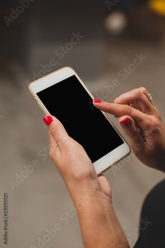 Mockup woman's hands holding black phone. Place for text or presentation website.
