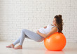A young pregnant woman is engaged in fitness on the floor. The concept of pregnancy health.