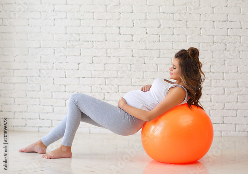 Naklejka A young pregnant woman is engaged in fitness on the floor. The concept of pregnancy health.