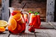 Leinwanddruck Bild - Homemade red wine sangria with orange, apple, strawberry and ice in pitcher  and glass on wooden background