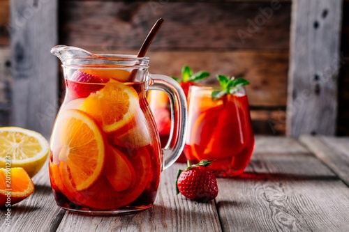 Leinwanddruck Bild Homemade red wine sangria with orange, apple, strawberry and ice in pitcher  and glass on wooden background