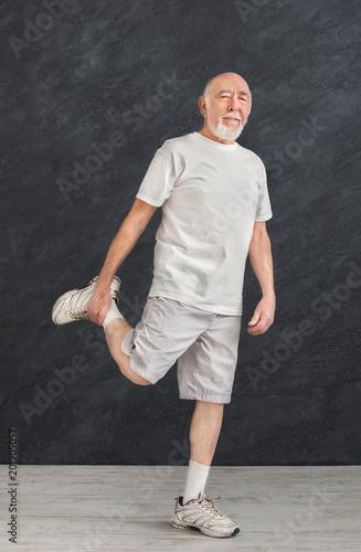 Wall mural Senior man stretching legs indoors