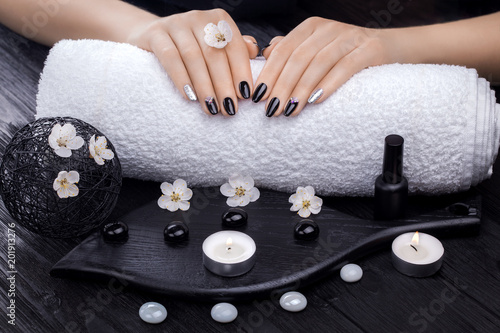 Plexiglas Manicure beautiful black manicure with apricot flower and towel on the wooden table. spa
