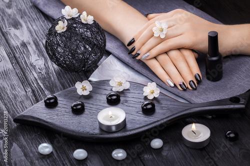 piękny czarny manicure z moreli kwiat i ręcznik na drewnianym stole. spa