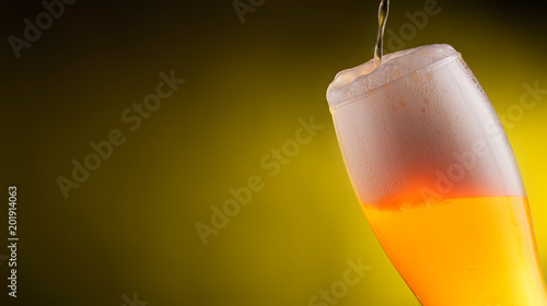Foto Murales Cold light Beer in a glass with water drops.