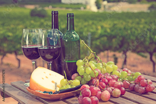 Foto Murales Red wine, cheese and grapes against vineyard