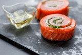 Delicious Salmon rolls, goats cheese in paper with knife, aromatic herbs, spices and rosemary oil in wave glass on old black stone background, clean eating, healthy food, diet or cooking concept - 201918417