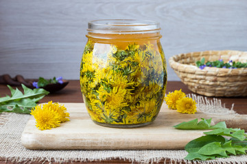 A glass jar filled with dandelion flowers and honey