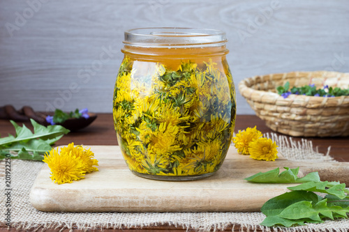 A glass jar filled with dandelion flowers and honey - 201922250