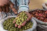 green cardamom in the hands of a man - 201924480