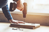 mans hands working with electric screwdriver and wooden plank - 201926612