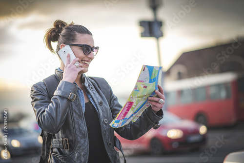 Foto Murales Confused female tourist in a foreign city using a map, trying to navigate herself around the city