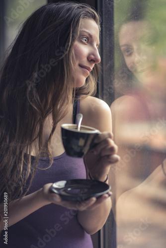 Młoda przypadkowa kobieta pije kawę espresso od filiżanki, opiera przeciw okno, cieszy się widok outdoors