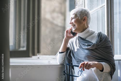 Rozochocona starsza starsza dama ma telefon rozmowę obok dużego okno w jej domu