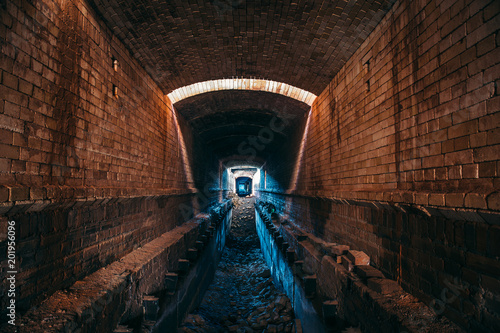 Długi podziemny tunel ceglany lub korytarz przemysłowy, atmosfera przerażająca i grozy, perspektywa