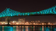 Long exposure shot of Jacques Cartier Bridge Illumination in Montreal, reflection in water. Montreal, Canada