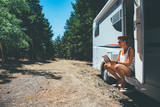 Girl reads on a motor home door step - 201981463