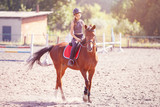 Young teenage girl riding her horse at the training on summer day - 201983670
