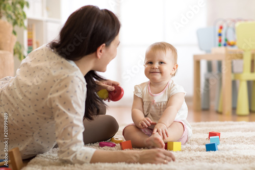 Nanny or babysitter looks after kid toddler. Baby girl playing with educational toys in nursery. Child having fun with colorful different toys at home. © Oksana Kuzmina