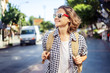 Beautiful young woman in sunglasses with a backpack on the street background. Travel, freedom, youth, student life