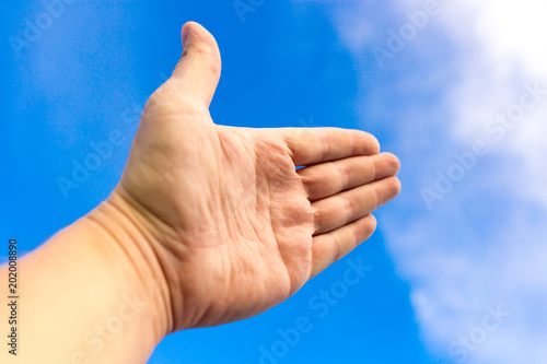 Male hand against a blue sky with clouds
