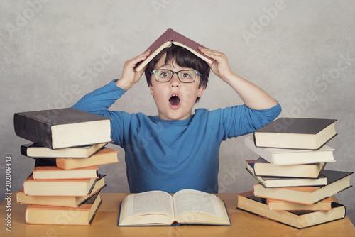 niño sorprendido con libros sobre una mesa © esthermm