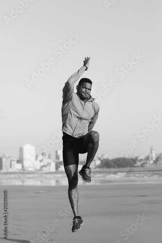 Foto Murales Black male runner doing jumps for warming up before running workout at the beach.