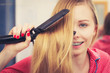 Woman straightening her long blond hair
