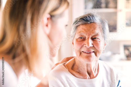 Foto Murales An elderly grandmother with an adult granddaughter at home.