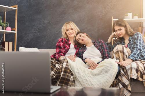 Uśmiechnięte młode kobiety ogląda film w domu