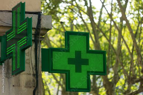 Fotobehang Apotheek Closeup of a green pharmacy sign outside a pharmacy store in France.