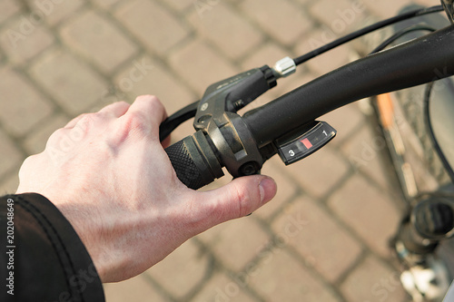 Hand on the bike handle on a summer sunny day