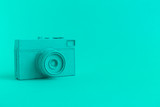 Flat lay of turquoise colored retro camera surrealism abstract concept