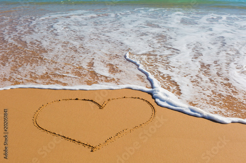 Foto Murales Picture of the heart on wet beach sand with the turquoise sea on background