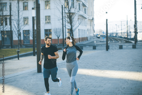 Fototapeta Healthy runners running in city with cityscape in background